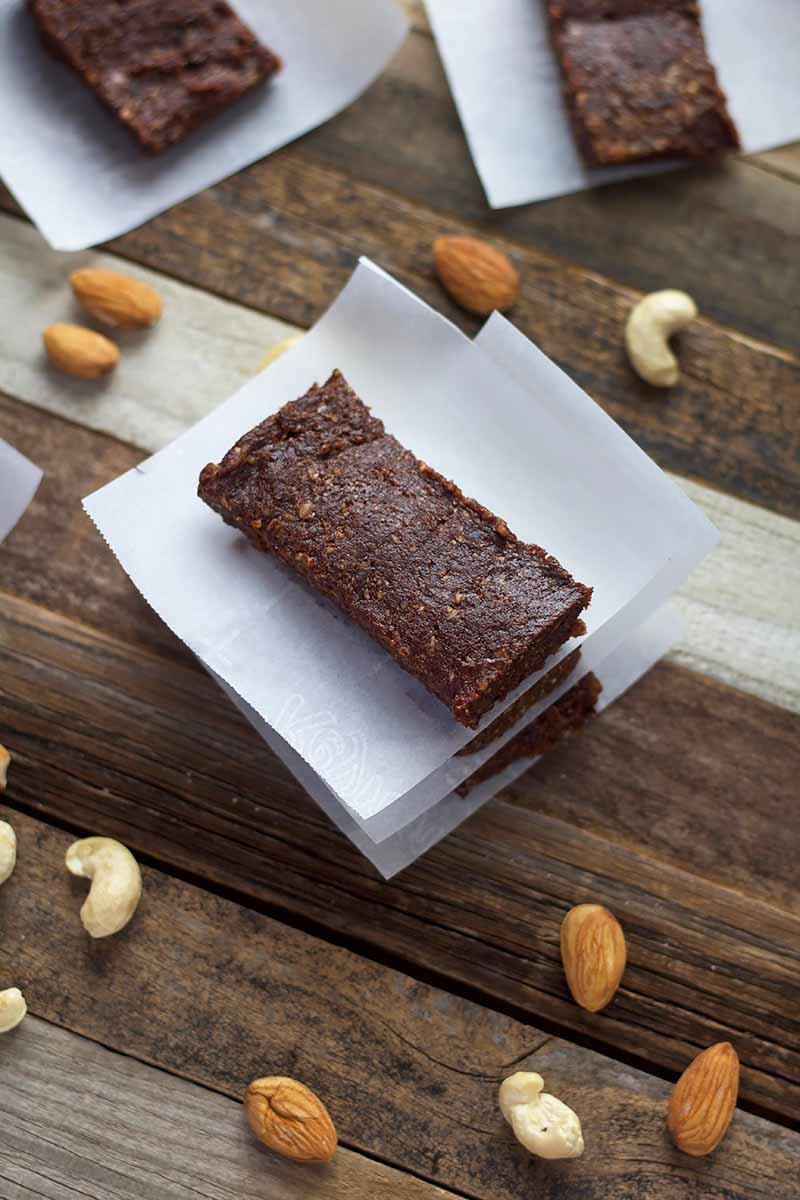 Vertical image of a small stack of fruit and cocoa bars with parchment paper between each one on a wooden surface with cashews and almonds.