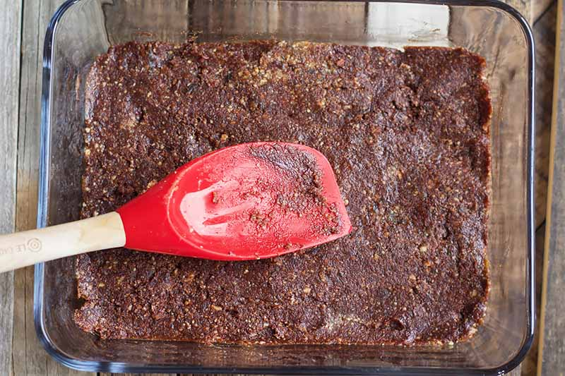 Horizontal image of a red spatula pressing down a brown batter in a glass pan.