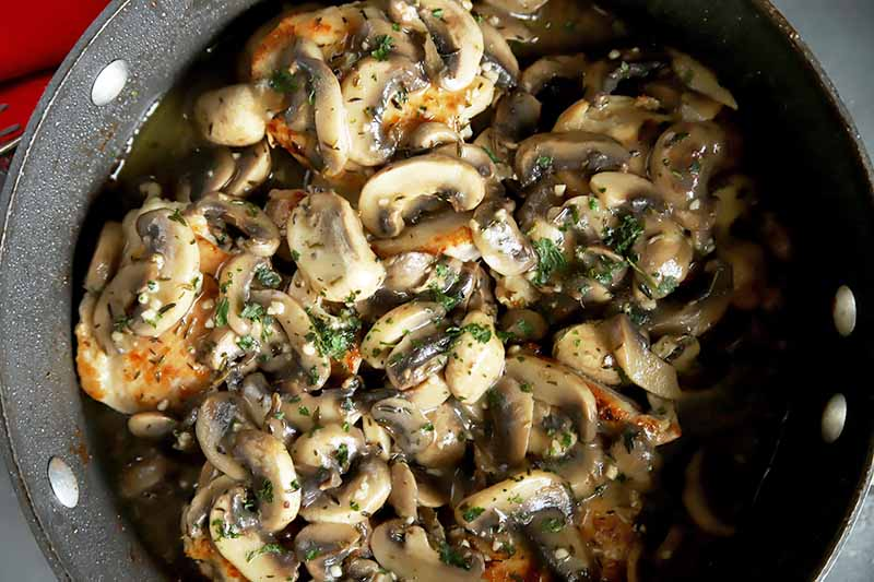 Horizontal image of a saucepan with herbed button mushrooms on top of seared poultry thighs.