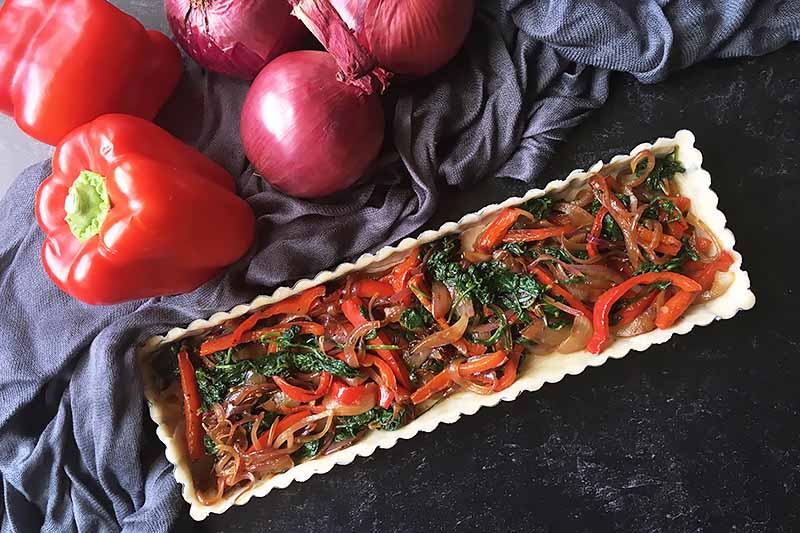 Horizontal image of an unbaked tart with cooked peppers, onions, and spinach.