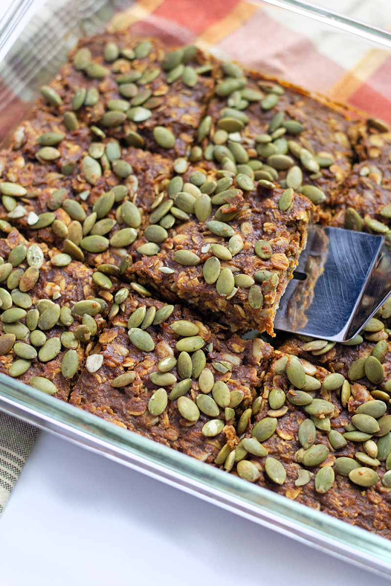 Vertical image of a spatula picking up a square of a granola bar topped with seeds.