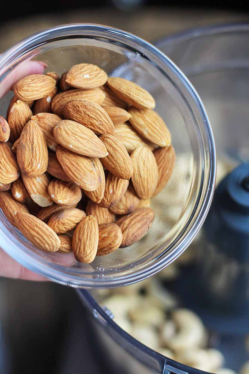 Vertical close-up image of a bowl of whole raw almonds.