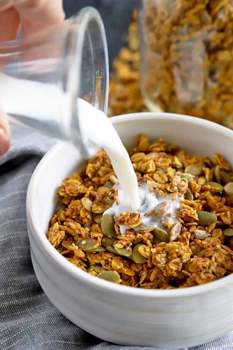 Vertical closely cropped image of a hand pouring milk from a glass fluted bottle into a white ceramic bowl of granola with pumpkin seeds.
