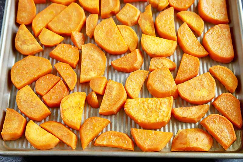 Horizontal overhead image of a metal baking sheet of peeled orange sweet potato slices that have been peeled and cut into half-moons.