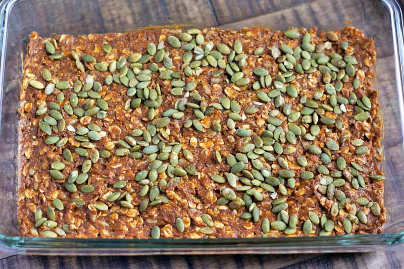 Horizontal image of a glass baking dish with a dark orange oat baked good topped with pumpkin seeds.