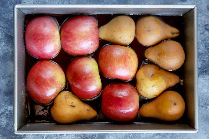 Overhead horizontal image of three halved apples and three halved pears arranged cut side down in a rectangular metal baking pan, surrounded by a brown liquid, on a gray surface.