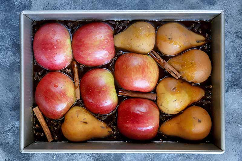 Horizontal overhead image of halved apples and pears arranged cut side down in a metal baking pan with whole cinnamon sticks and cloves in a brown liquid, on a gray speckled background.