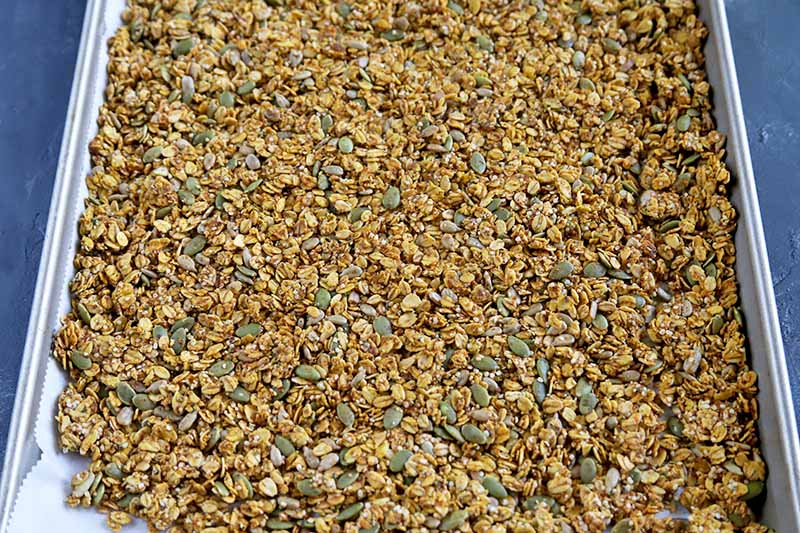 Horizontal overhead closely cropped image of an oat and seed mixture spread in a thin layer in a large metal baking sheet, on a gray surface.