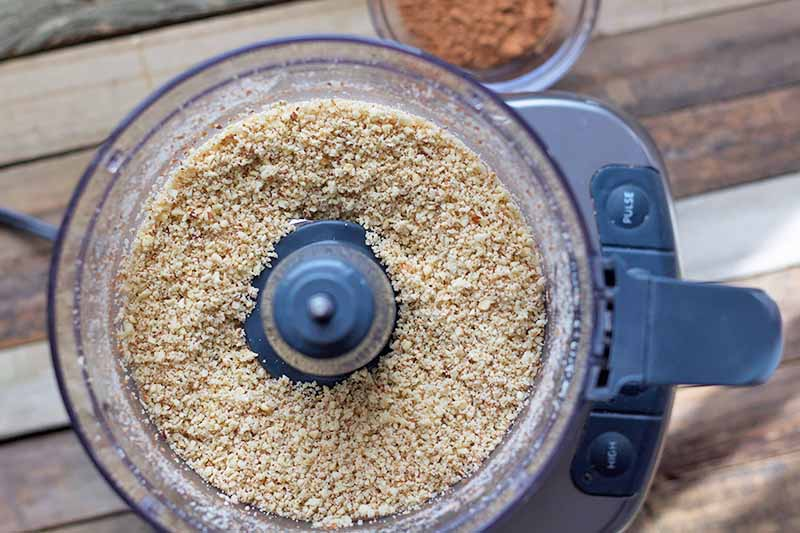 Horizontal image of a food processor with a dry, pulverized brown mixture.