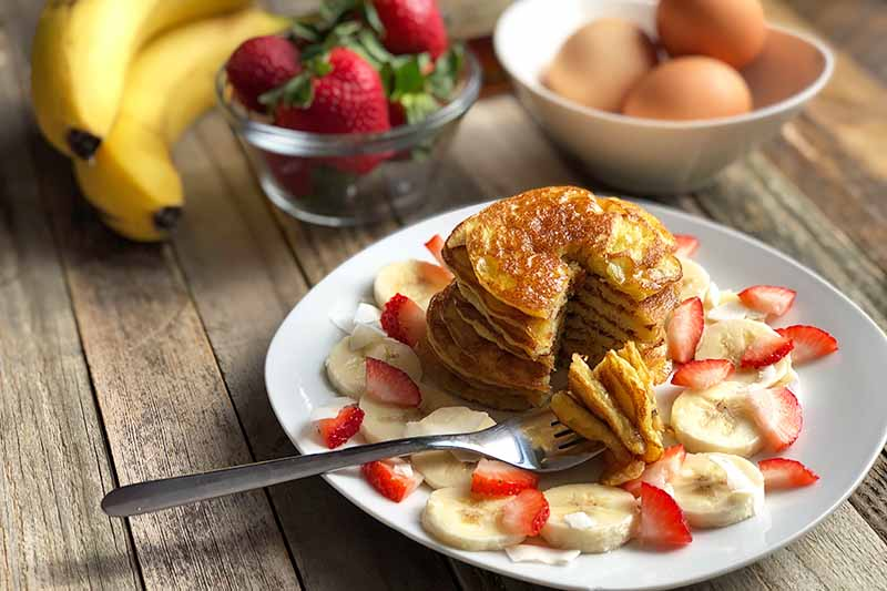 Horizontal image of a stack of pancakes on a white bowl with sliced fruit, with bananas and bowls of strawberries and eggs in the background.