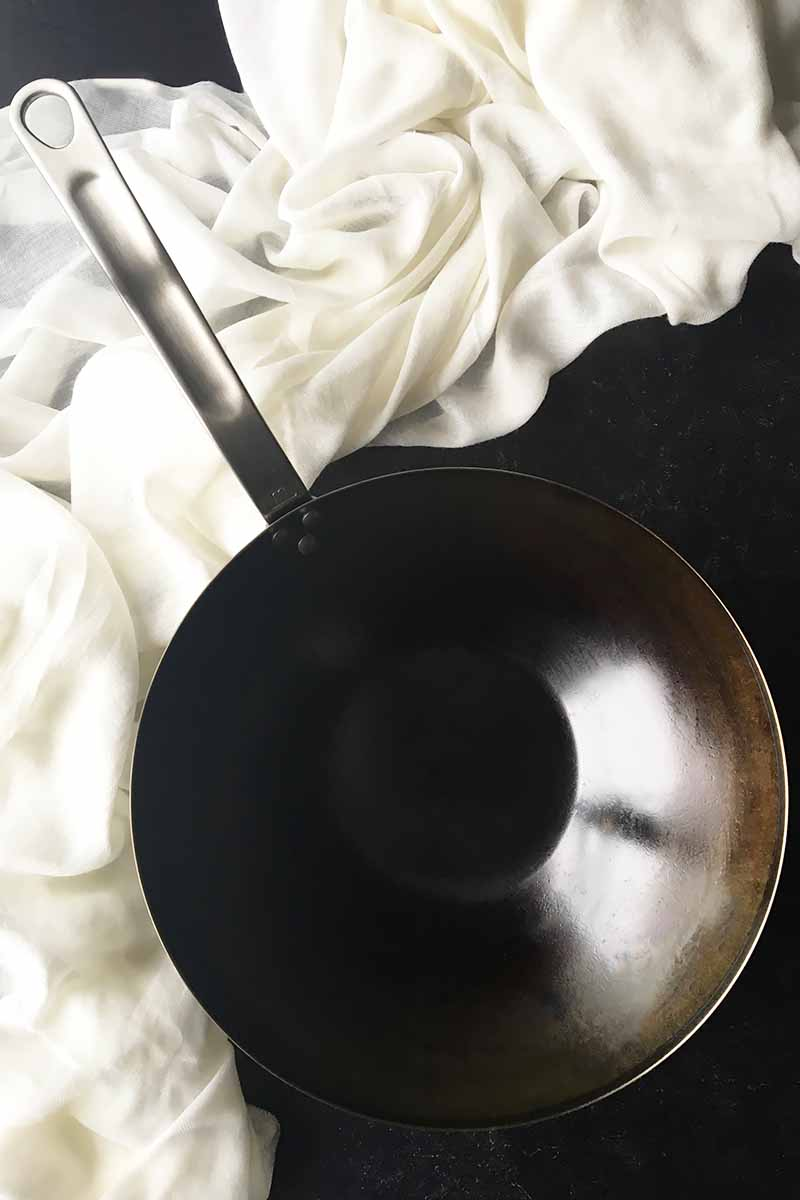Vertical image of a wok pan with a white towel.