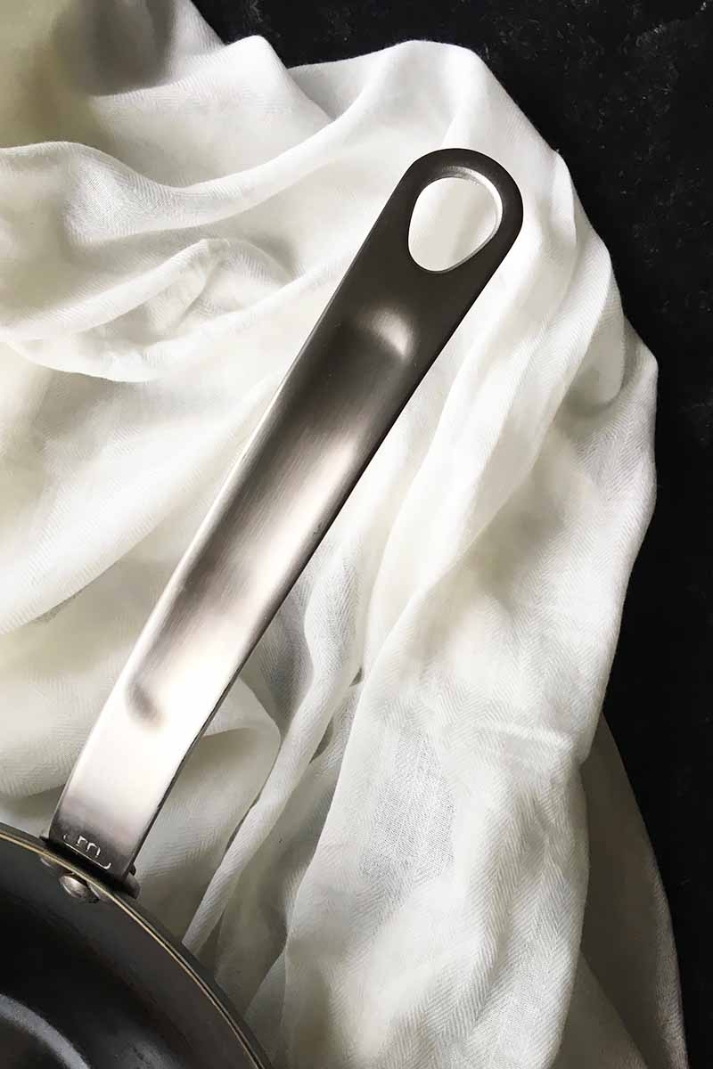 Vertical image of a silver handle with a hole on the top, on a white towel.