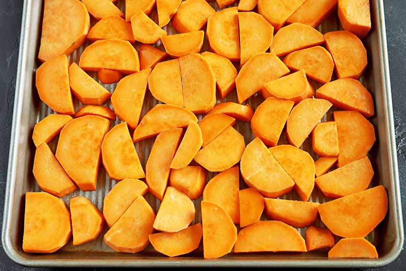 Horizontal overhead image of a metal baking pan of raw peeled and sliced sweet potato cut into rounded half-moons.