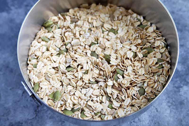 Horizontal closely cropped overhead image of a stainless steel bowl of oats and pumpkin seeds, on a blue-gray sponge painted surface.