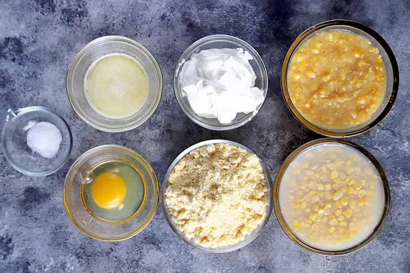 Horizontal overhead image of one small and six medium-sized bowls of salt, egg, melted butter, sour cream, cornmeal baking mix, and canned whole kernel and creamed corn, on a sponge-painted blue-gray and white surface.
