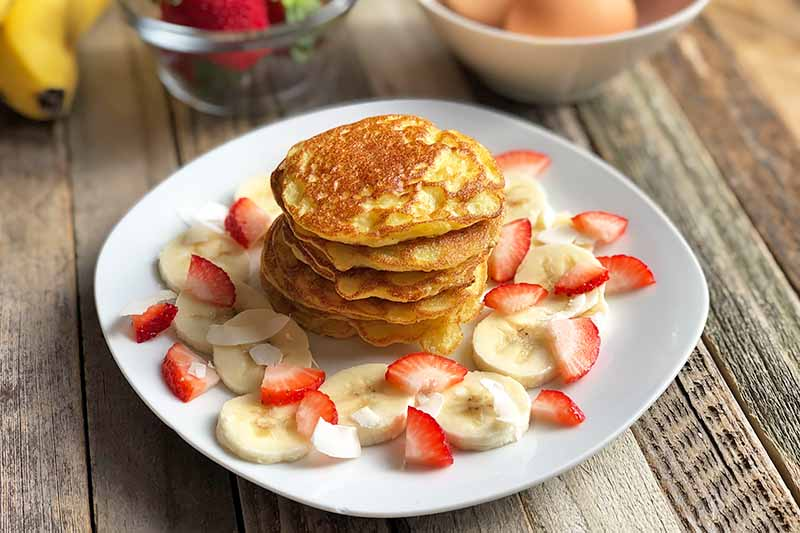 Horizontal image of a stack of small pancakes on a white plate with fresh fruit.