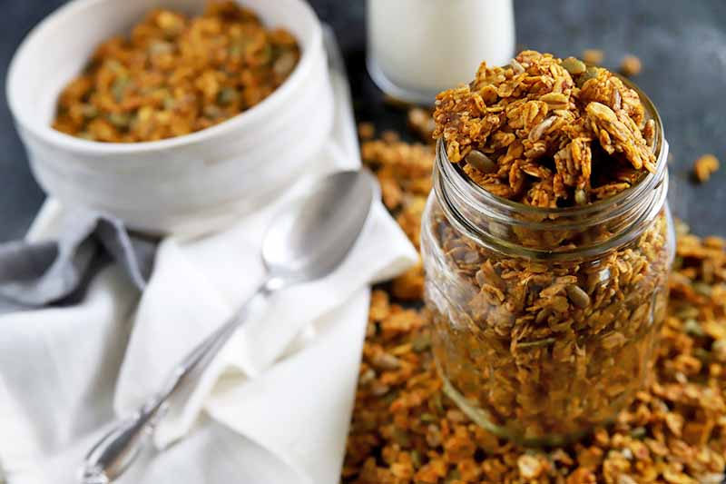 Horizontal image of a jar overfilled with homemade granola to the right with more spilling out around it on a gray surface, with a crumpled white cloth napkin, white bowl of cereal, and spoon to the left.