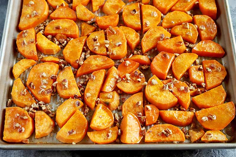 Horizontal image of roasted sweet potatoes spread out on a metal baking sheet in a single layer, topped with chopped pecans, brown sugar, and butter.