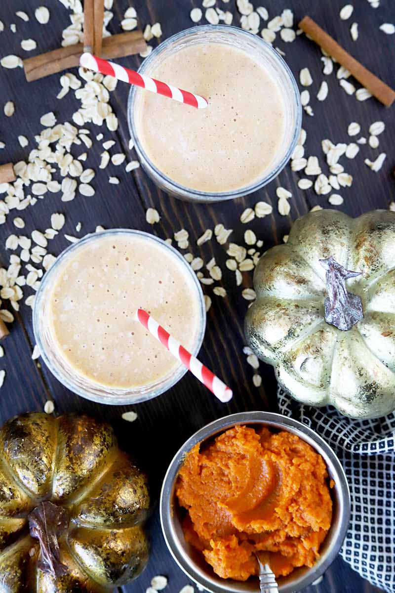 Vertical overhead image of two short glasses of pumpkin oatmeal smoothie with red and white paper straws, two gold metallic decorative pumpkins, a small bowl of orange squash puree, a gray-blue dish towel, and scattered uncooked rolled oats and cinnamon sticks, on a dark gray surface.