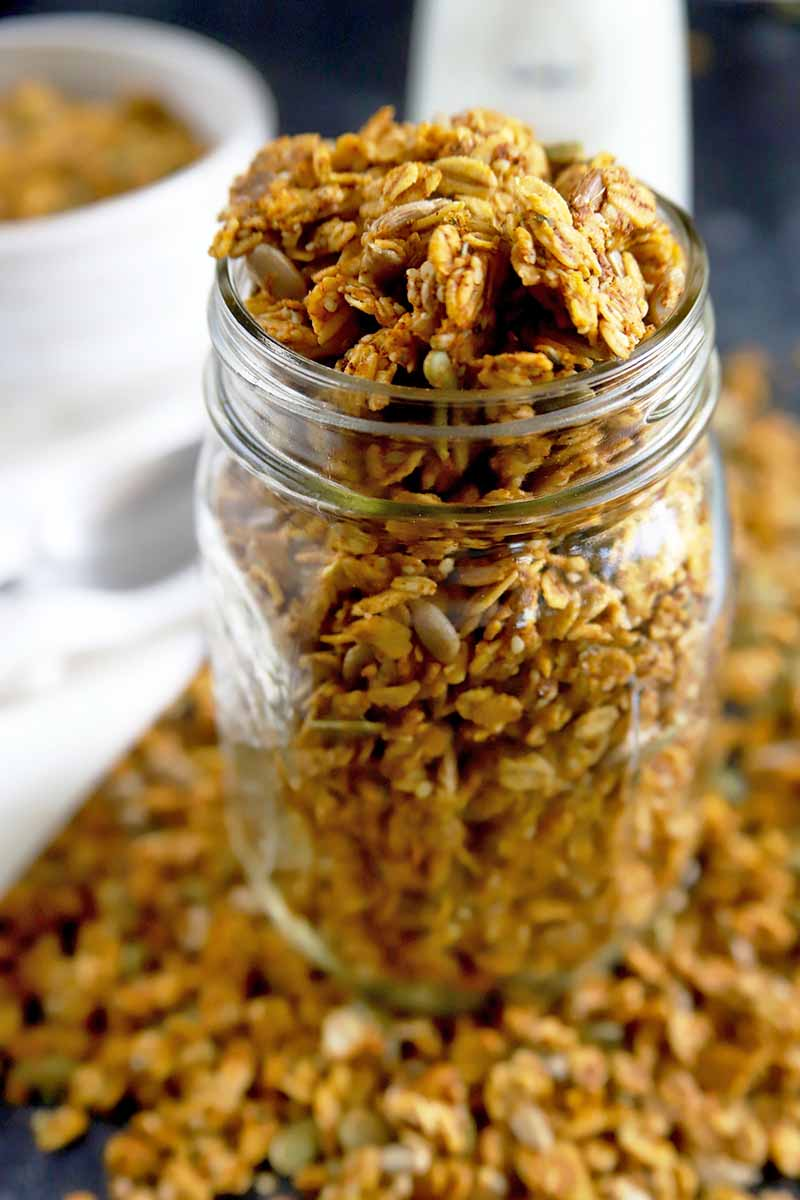 Vertical image of a glass jar overflowing with homemade granola, with more scattered on the surface, and a white cloth topped with a white ceramic bowl of cereal beside a glass bottle of milk in the background, against a gray backdrop, with selective focus.