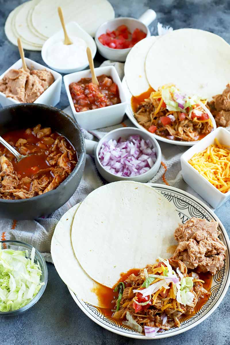 Vertical image of a huge table display with tortillas, shredded chicken, and assorted toppings on plates and in bowls.