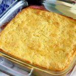 Horizontal oblique overhead image of a square glass baking dish filled with a golden brown corn casserole, on a white surface wit ha red cloth and a stick of butter on a ceramic dish.