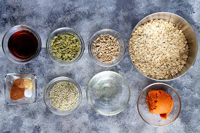 Overhead horizontal image of one small square and six small glass bowls of maple syrup, spices, pumpkin seeds, flax seeds, hemp seeds, and pumpkin puree, and a larger stainless steel bowl of uncooked oats, on a mottled gray and white surface.