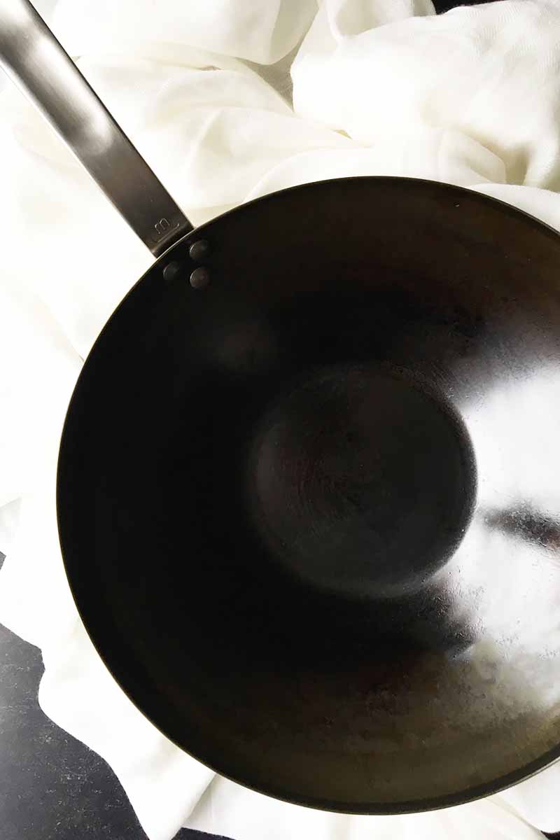 Vertical image of a seasoned wok pan on top of a large white towel.