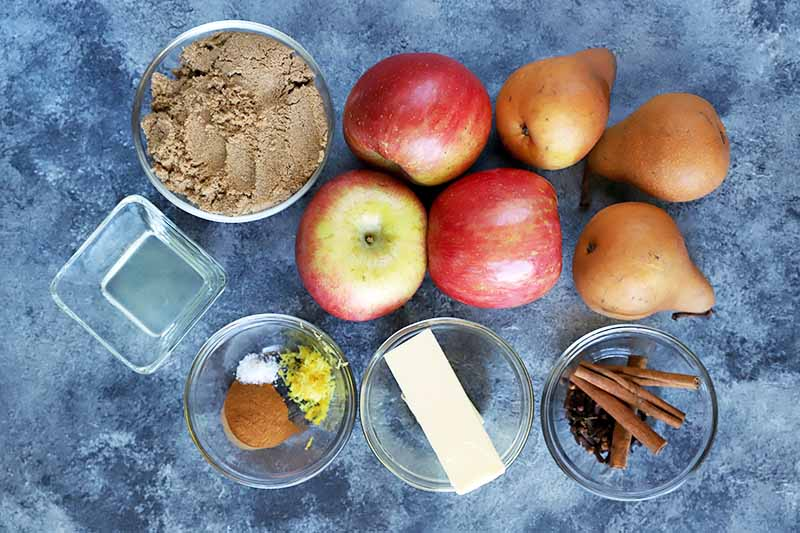 Horizontal overhead image of four round and one square small glass bowl or brown sugar, lemon juice, cinnamon, salt, lemon zest, butter, whole cinnamon sticks and cloves, with three whole red apples and three whole brown pears, on a sponge painted blue-gray surface.