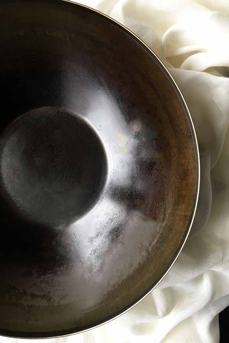 Vertical image of a seasoned and naturally discolored wok pan on a white towel.