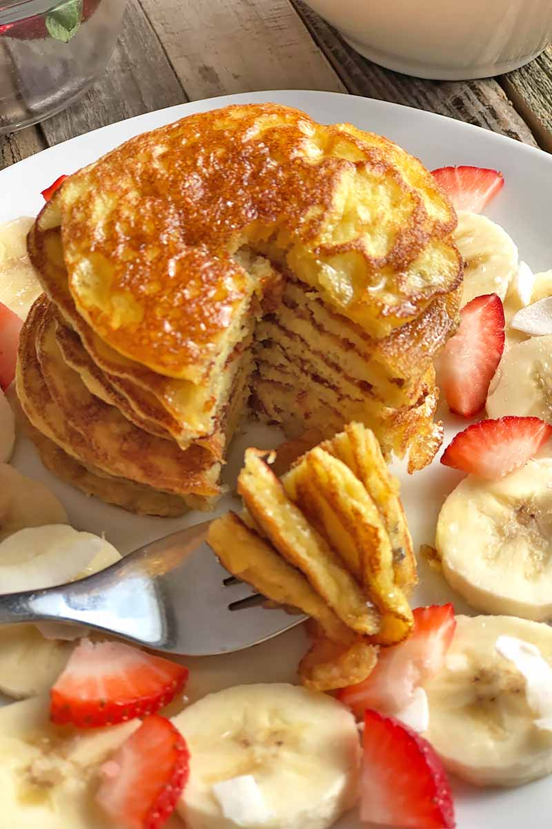 Vertical close-up image of a stack of pancakes with pieces on a metal fork, surrounded by sliced fresh fruit.