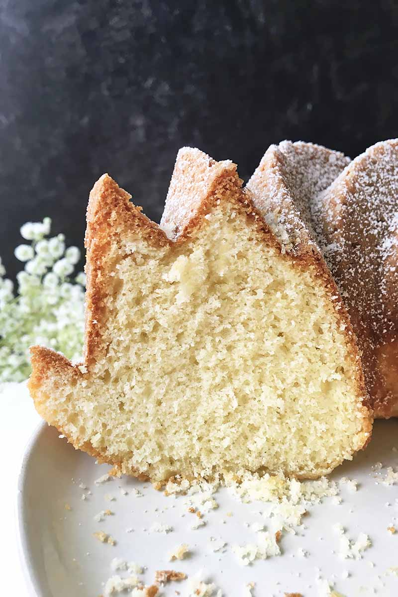Vertical close-up image of a bundt cake with a slice out of it on a white plate with crumbs.