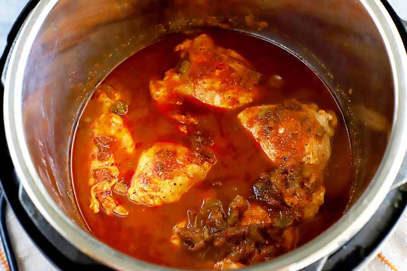 Horizontal image of a slow cooker with poultry, red sauce, and seasonings.