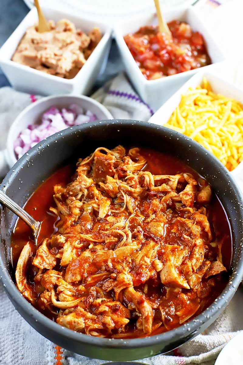 Vertical image of a bowl of cooked shredded chicken in a red sauce surrounded by condiments in white bowls.