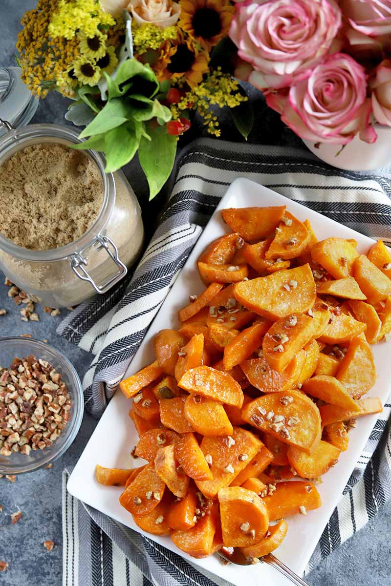 Horizontal overhead closely cropped image of a white ceramic rectangular platter of roasted butter pecan sweet potatoes on a striped gray and white cloth, with a small dish of chopped pecans and a glass swingtop jar of light brown sugar to the left, and two vases of yellow and pink flowers at the top of the frame, on a gray surface.