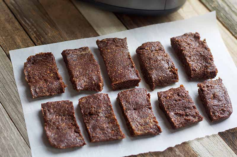 Horizontal image of two rows of cocoa snack bars on a parchment paper.
