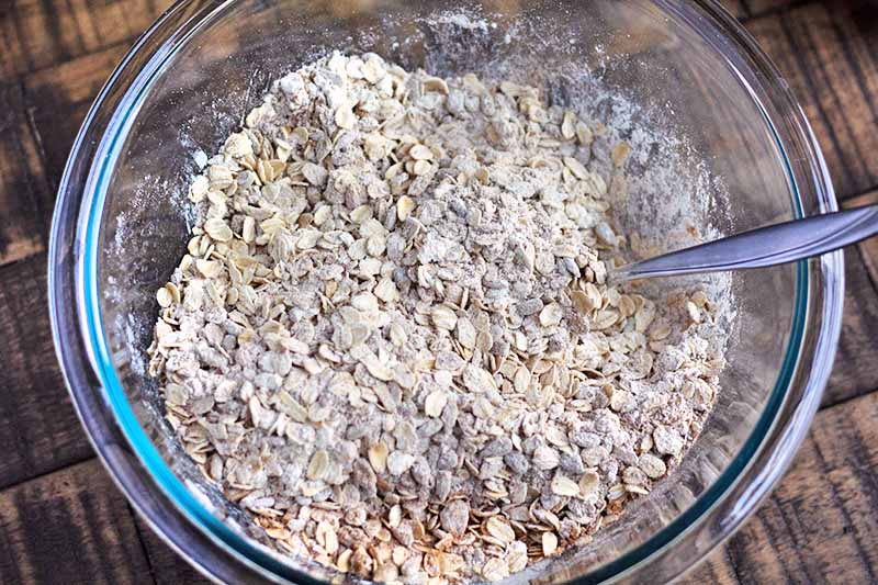 Horizontal image of an oat and dry ingredient mixture in a glass bowl.