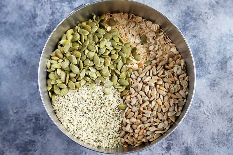 Horizontal overhead image of a stainless steel bowl with separate quadrants of pepitas, hemp seeds, sunflower seeds, and oats filling the bottom, on a gray and white spongepainted background.