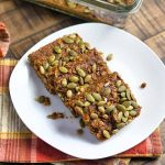 Horizontal image of shingled pumpkin squares topped with pumpkin seeds on a white plate with a plaid towel.