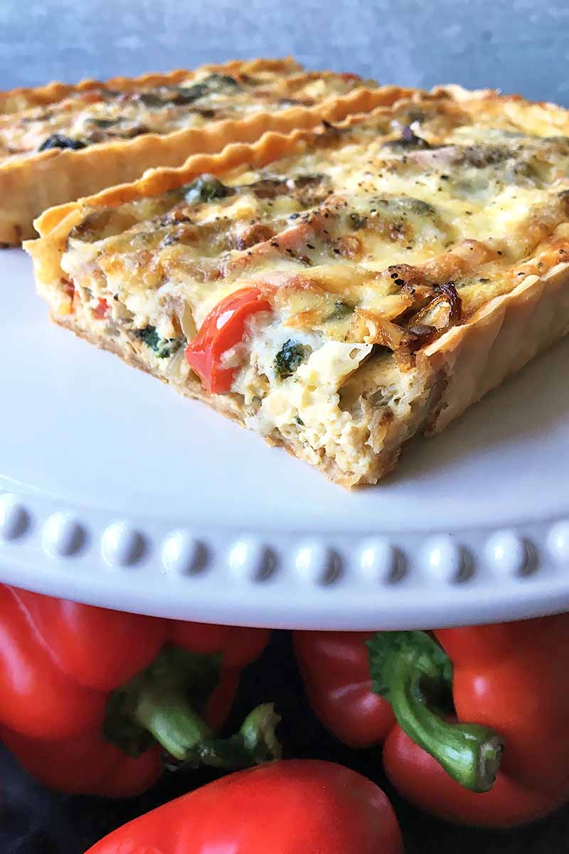 Vertical image of a white cake pan with quiche on top, and red peppers on the bottom.