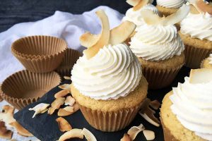 Horizontal image of decorated cupcakes with toasted coconut garnishes.