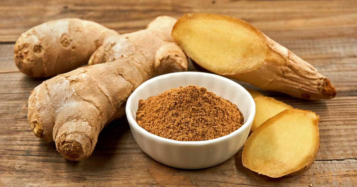 Fresh ginger roots and powdered ginger on a rustic wooden surface.