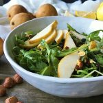 Horizontal image of a white bowl with arugula and pears