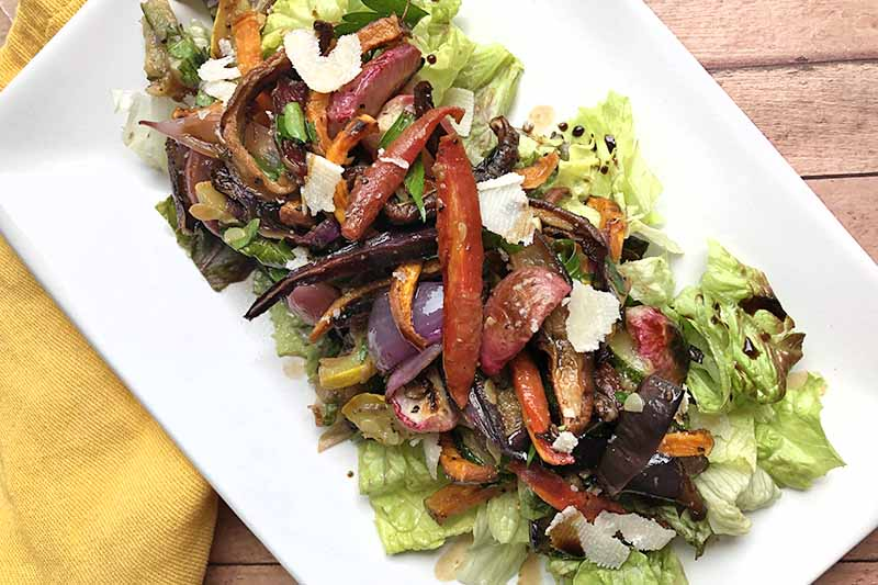 Horizontal closely cropped overhead image of a white rectangular serving platter of lettuce topped with roasted vegetables, dressing, and shaved Parmesan cheese, on a wood surface with a yellow cloth napkin at the left of the frame.