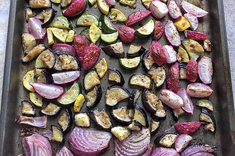 Horizontal overhead image of a metal baking sheet of roasted zucchini, radishes, yellow squash, and purple onion.