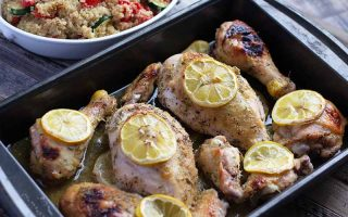 Horizontal image of chicken pieces in a dark pan topped with lemons, next to a quinoa and vegetable side dish.