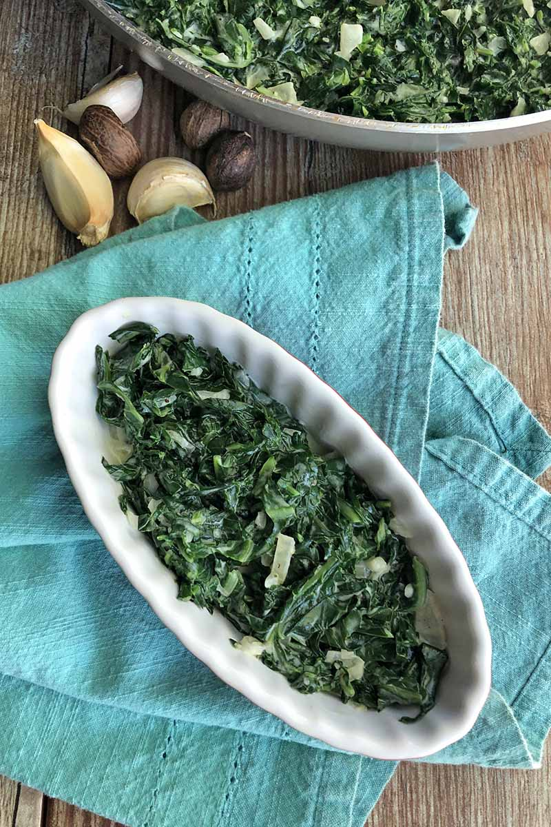 Overhead vertical image of an oblong ceramic dish of creamed collard greens with more in a frying pan at the top of the frame, with whole nutmeg and cloves of garlic, and a folded blue-green cloth, on a brown wood surface.