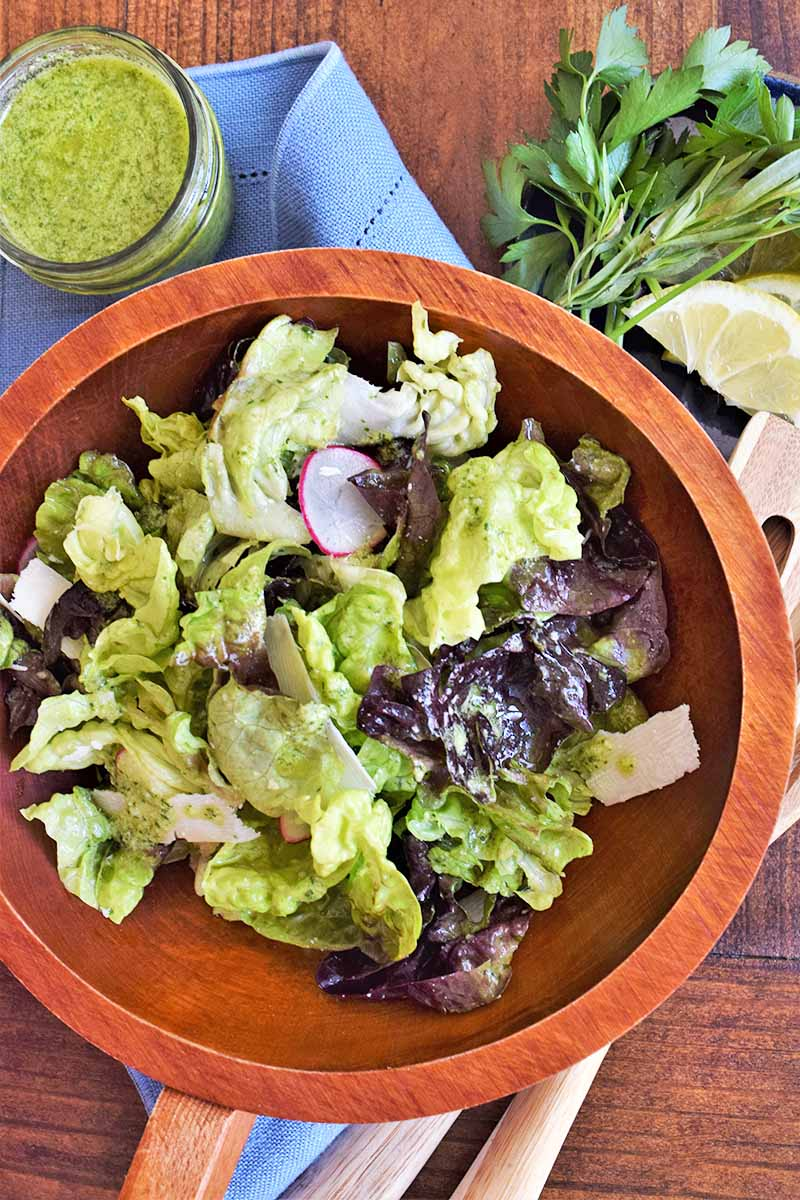 Overhead vertical image of a wooden bowl filled with salad tossed in dressing, on a brown wood surface with a blue cloth napkin, a jar of pesto dressing, sprigs of fresh herbs, and wooden serving utensils.