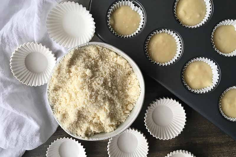 Horizontal top-down image of a white bowl with a sandy powder next to batter in mini cupcake tins.