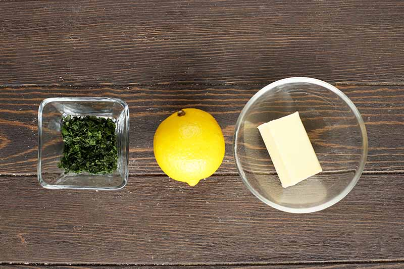 Horizontal image of fresh herbs, a whole lemon, and butter.